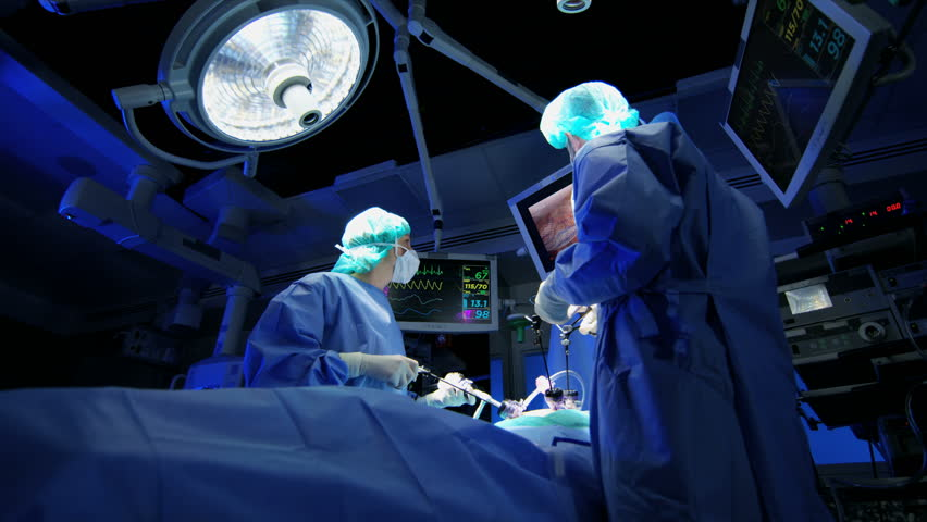 Medical Caucasian hospital specialist team in scrubs training in the operating theatre in Laparoscopy surgery using Endoscope technology with monitors equipment RED WEAPON