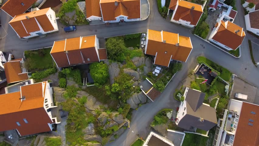 Aerial shot flight over the European city Skudeneshavn, Norway. View from above on the roofs of houses, beautiful gardens, lawns, roads in the summer. Quiet European suburbs.