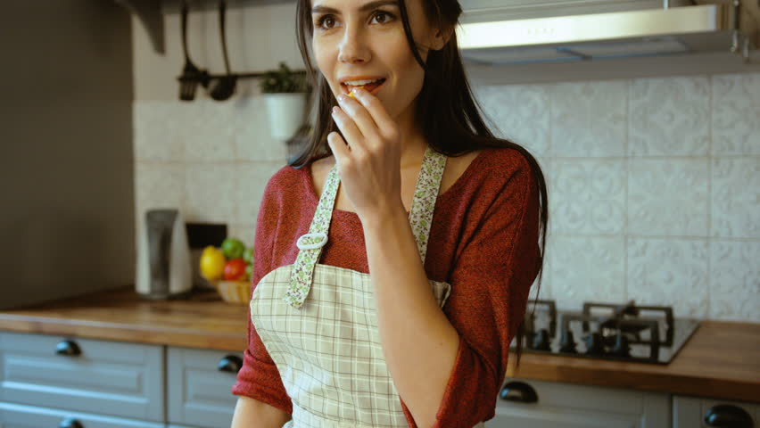Close up portrait of attractive young woman cooking in the kitchen and trying ingredients. Smiling at the camera.