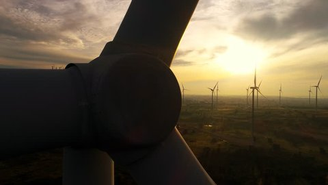 4k drone footage of wind farm turbines at sunrise with clouds