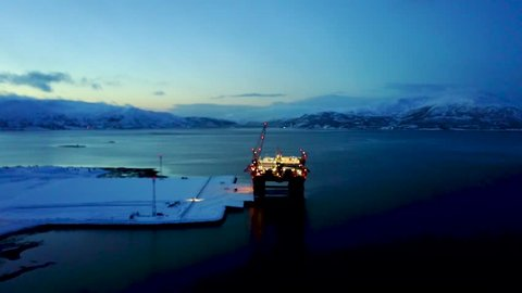 Aerial of arctic oil drilling platform rig during polar night sunset - Norway