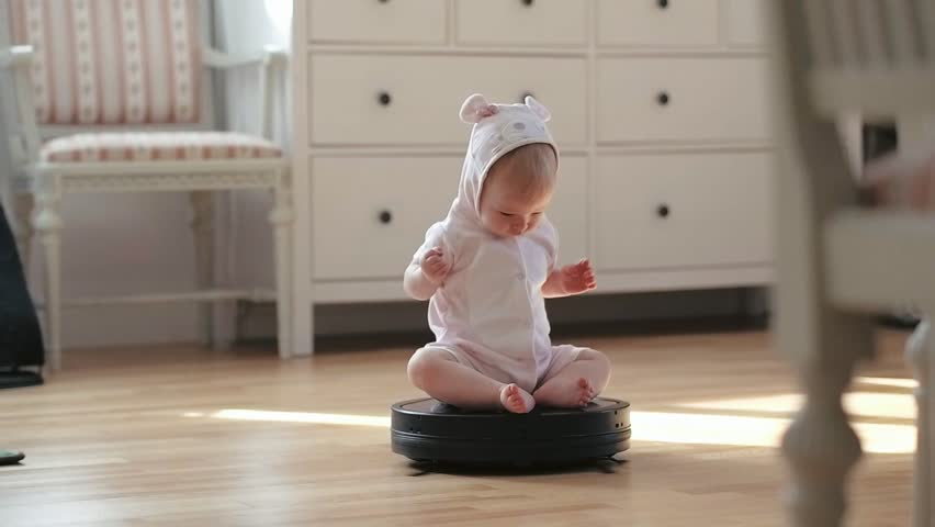 Little baby girl rolling on moving robot vacuum cleaner while cleaning home
