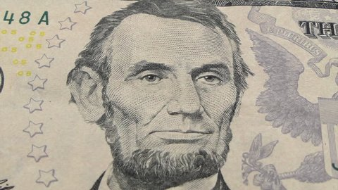 Macro zoom of Abraham Lincoln on the US five dollar bill.