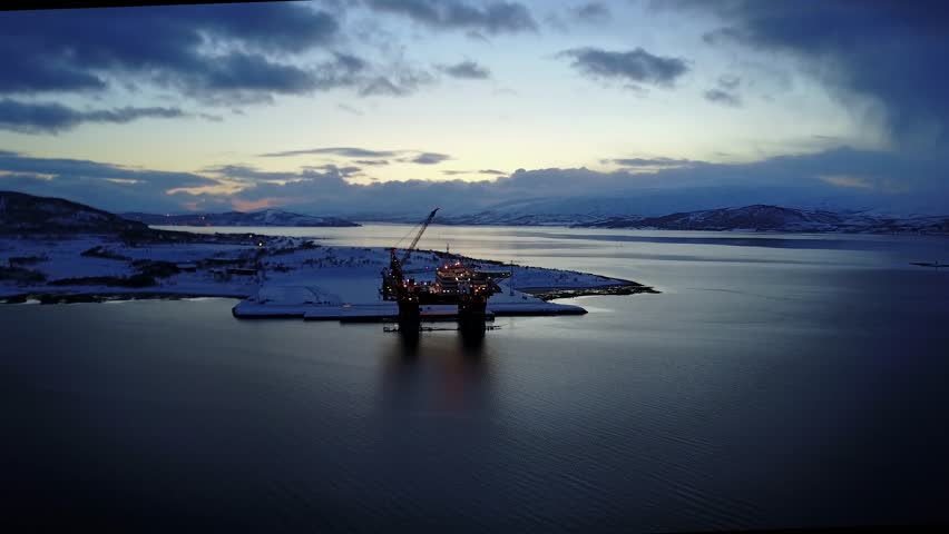 Aerial of arctic commercial oil drilling platform docked at sunset
