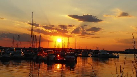 Evening marina port in Sozopol, Bulgaria. Yachts and ships against backdrop of sunset.