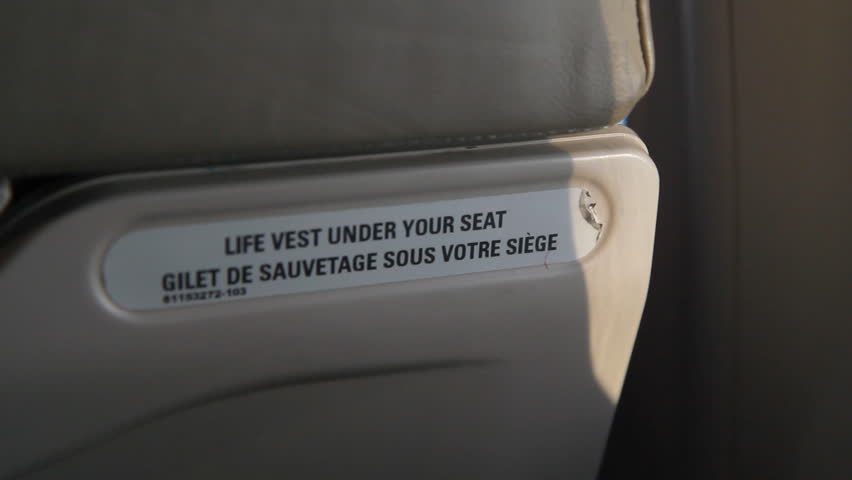 Detail of plane seat with 'Life vest under your seat' notice. Rack focus at end of shot. Inflight on a commercial turboprop plane.