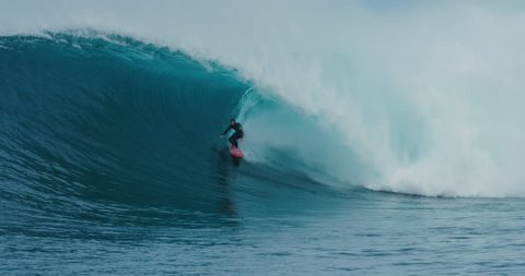 Surfer rides giant blue ocean wave. Shot on RED in 4k. Big wave surfing. Slow motion