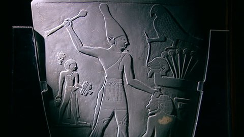 CAIRO, EGYPT - CIRCA 2002: CU dramatic raking light highlighting King Narmer wearing the White Crown of upper Egypt, wielding a mace in readiness to bludgeon an enemy. Narmer Palette, Museum of Cairo.