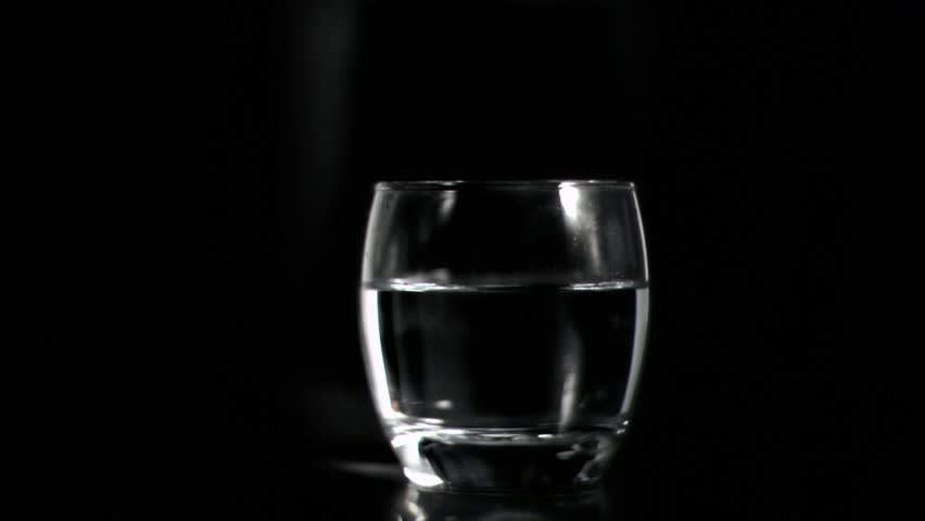 Vodka splashing in super slow motion against black background