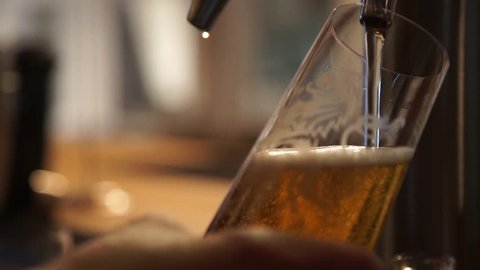 Pouring a beer in glas at the bar , beer tap