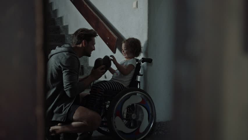 Young father taking care of his disabled child on a wheelchair | Shutterstock HD Video #30571168