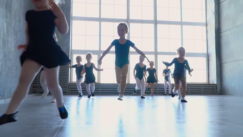 Children from ballet school run in embraces of the teacher of the ballerina. Little girls of the ballerina run to embrace the teacher. Beautiful and stately ballet teacher in the classroom teaches