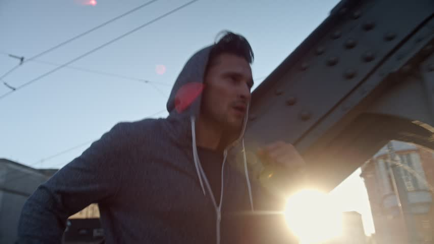 Handsome young boxer jogging in urban surroundings