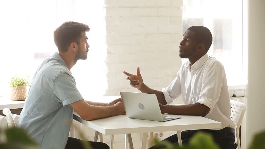 African american and caucasian young businessmen negotiating sitting at office desk with laptop, two satisfied partners close successful business deal with investor, handshake after making agreement
