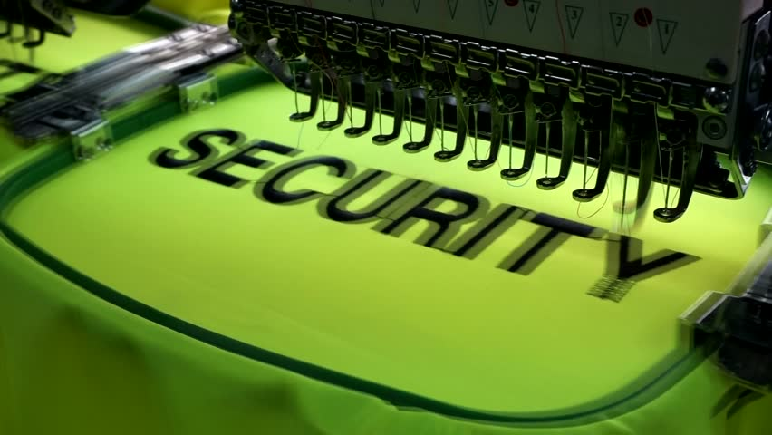 "Embroidery Machine are embroidery wording ""SECURITY"" on safety vest in Garment Manufacturers. Textile embroidery machine in Garment Manufacturers. Embroidery machine needle in Textile Industry. 