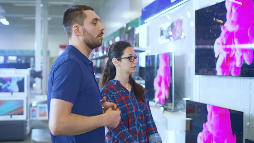 In the Electronics Store Professional Consultant Provides Expert Advice to a Young Woman Who Looks for a New 4K UHD TV to Buy. In This Bright, Modern Store all the Latest TV Models Are Hanging. | Shutterstock HD Video #30614458