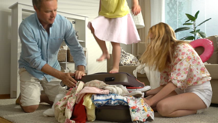 A Young Family with Child Trying to Close the Chock-full Suitcase. Slow motion