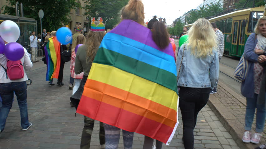 HELSINKI, FINLAND - JULY 01, 2017: Young women with rainbow flags. Thousands of people in solidarity during a Gay pride parade on the streets of Helsinki.