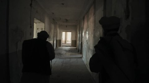 Two armed Mujahideen walk along the corridors of the abandoned building and hunt down the enemy