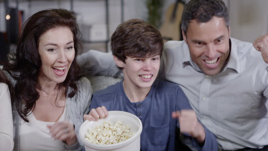 Happy caucasian family get very excited watching sports on television and the popcorn spills everywhere. In slow motion.
