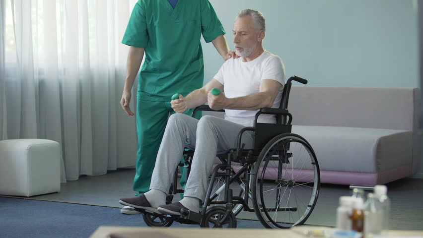 Male in wheelchair pumping his weak muscles with help of nurse, rehabilitation | Shutterstock HD Video #30659488