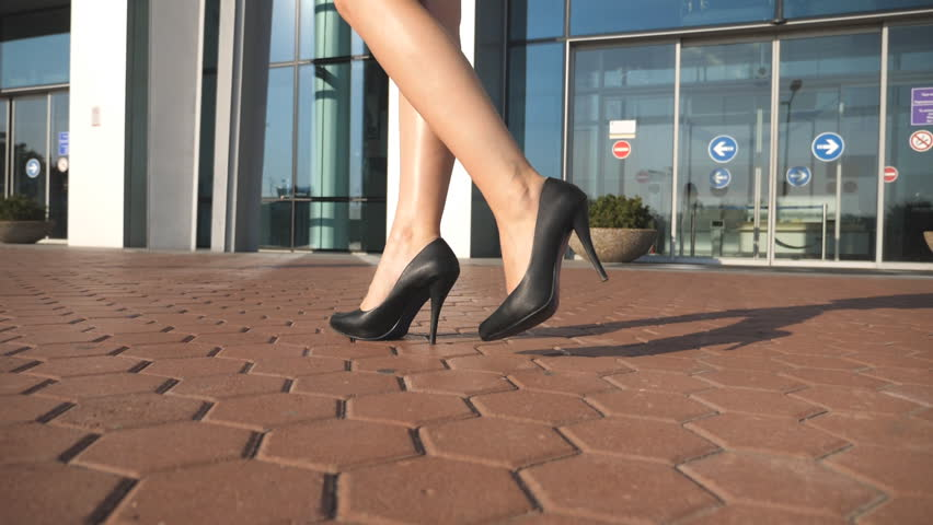 Feet of young woman in high-heeled footwear going in the city. Female legs in high heels shoes walking in the urban street with contemporary business office at background. Girl stepping. Slow motion | Shutterstock HD Video #30662998