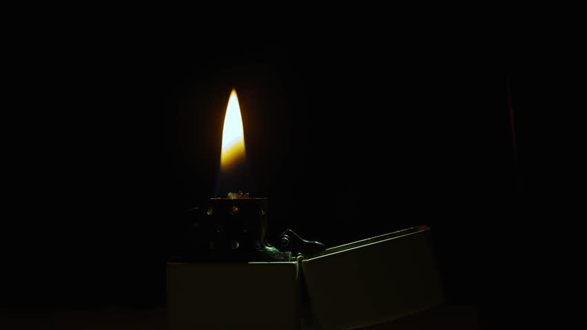 lighter zippo, a fire burns on a black background