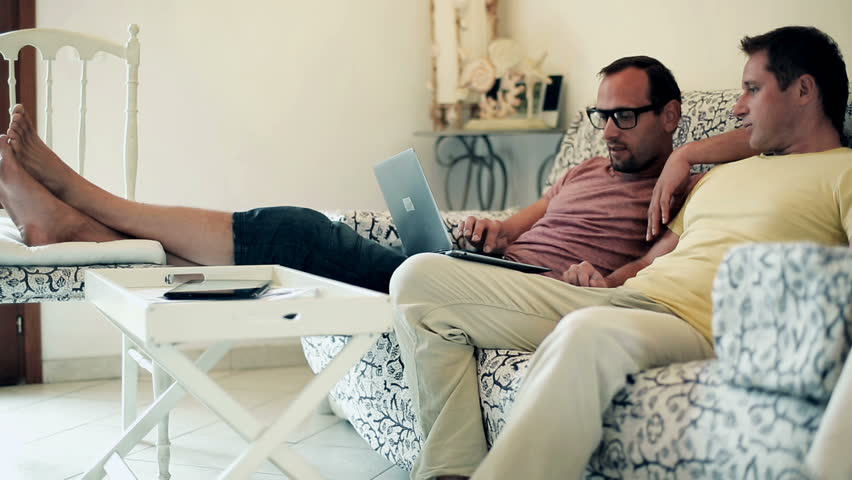 Two male friends on sofa using laptop computer