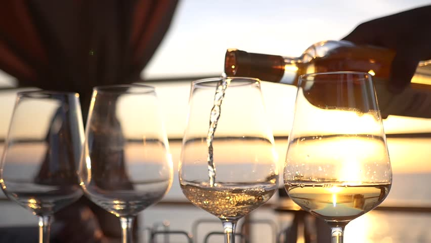 Pour white wine over clear glass glasses at sunset. HD, 1920x1080. slow motion