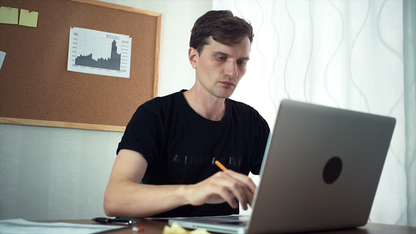Young businessman attaching sticky note and analyze graphs to board in the office. Freelancer working at home | Shutterstock HD Video #30681649
