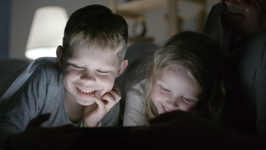 PAN of happy boy and girl playing on tablet laughing with grandfather in dark bedroom lit by lamp light | Shutterstock HD Video #30690538