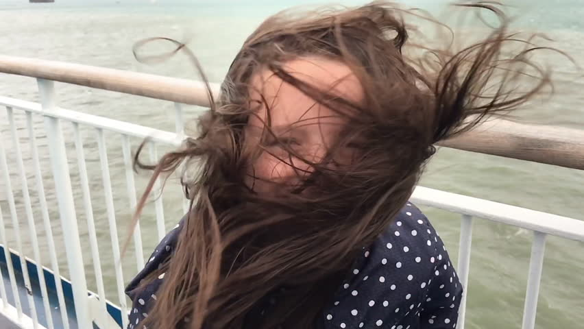 Girl smiling as she stands on a windy ferry deck with hair blowing everywhere. Filmed in slow motion