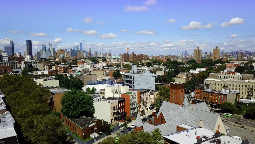 Brooklyn, NYC AERIAL PULL SLOW with Manhattan Skyline, 2017, Bedford-Stuyvesant area.