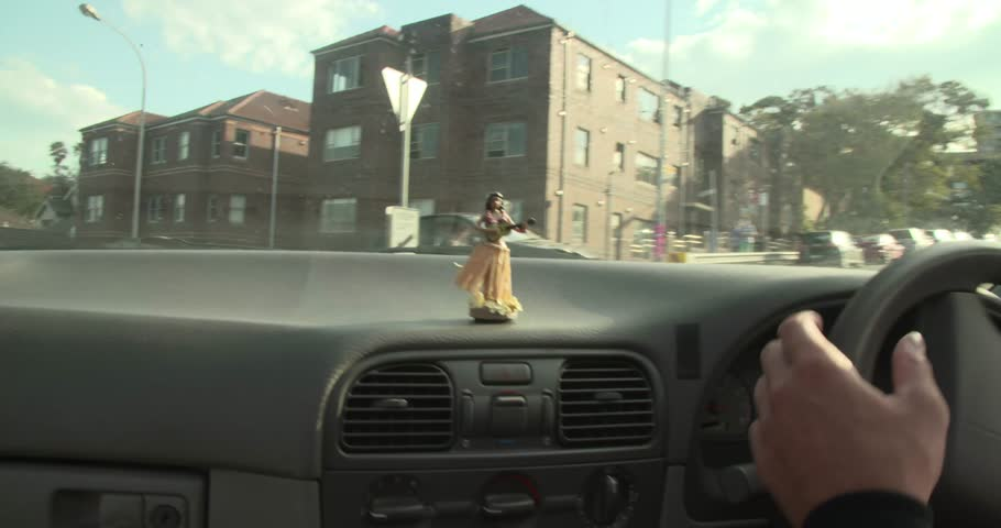 MS POV Figurine of Hula Dancer on dashboard of car driving through city, Bondi Beach / Sydney, New South Wales, Australia