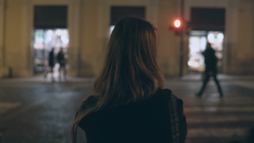 Young brunette woman crossing the traffic road in the evening and walking in the city centre alone, through the streets.