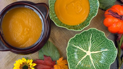 Serving hot pumpkin soup into green leaf bowls, on a rustic background for Happy Halloween or Thanksgiving party food, real time.
