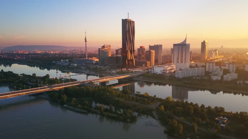 aerial view of vienna skyscrapers modern city at sunrise flying over danube bridge