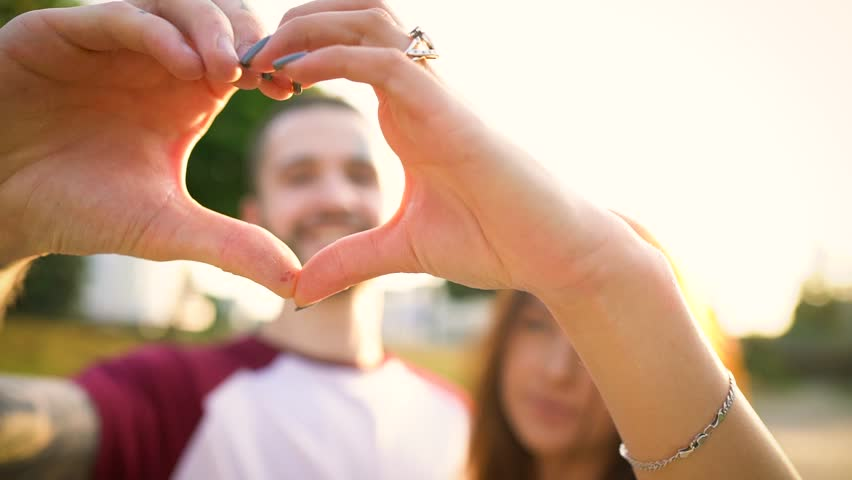 Young couple in love making heart symbol with their hands at sunset. Slow motion | Shutterstock HD Video #30761908