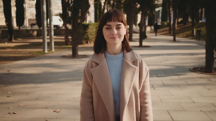 Camera follows young attractive hipster brunette puts earphones in her ears, turns on favourite music and walks around park, swaying and dancing in soft winter or autumn sunlight