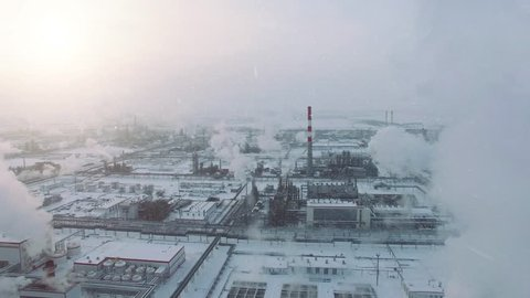 Storm weather and snowfall. Aerial view of gas processing plant at winter time. Cold morning at industrial zone