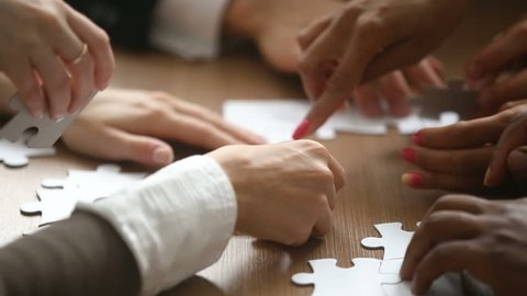 Close up view of hands assembling jigsaw puzzle on table, group of business people matching pieces playing board game, right decision making in business, help and support in teamwork concept