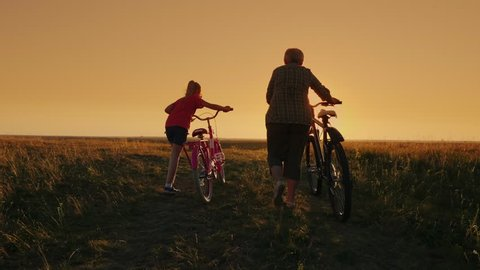 Communication of generations. Grandmother and granddaughter go together at sunset, drive bicycles.