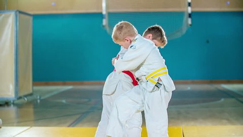 A boy with a yellow and red belt are wrestling. A boy with a red belt falls on the ground. The have a judo practice.