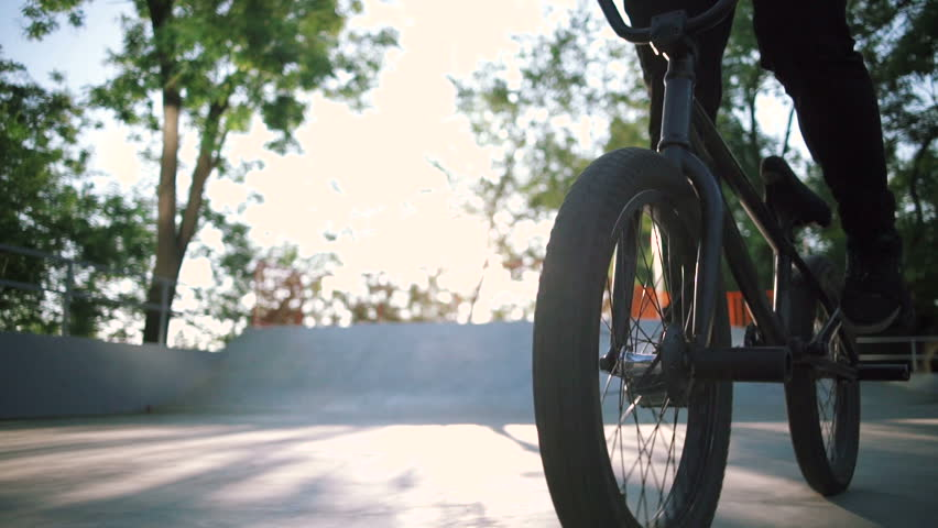 Close up shot of young man riding BMX bike in extreme park and doing tricks | Shutterstock HD Video #30860008