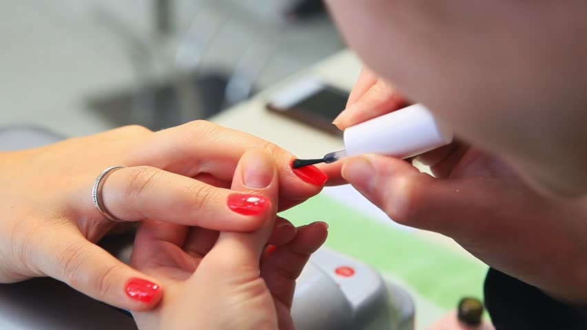 manicure making female hands, covering of transparent enamel and nail varnish, nail polish.Woman hands in a nail salon receiving a manicure by a beautician. Woman getting nail manicure, spa treatments