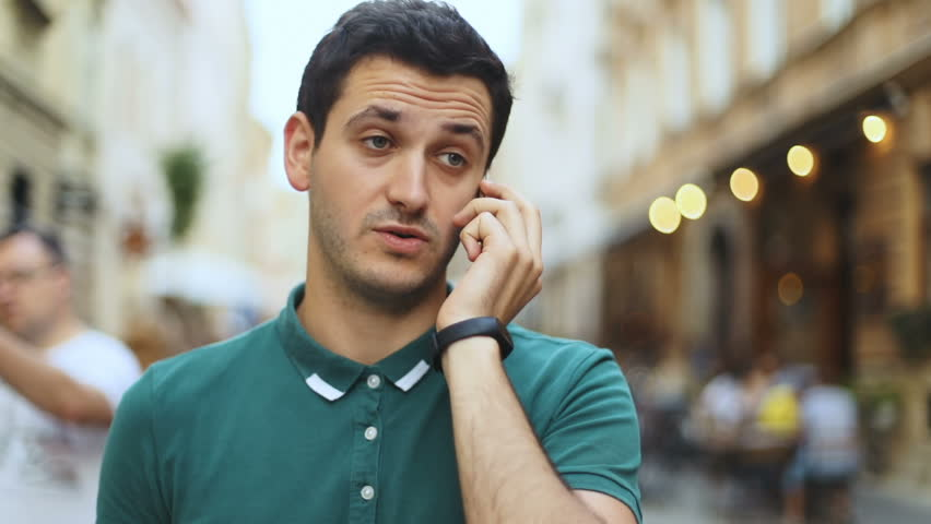 Stressed displeased disappointed man guy talking smart mobile phone outdoor city blurred street background quarrel angry expression face portrait annoyed businessman busy problems upset emotion speak | Shutterstock HD Video #30871531