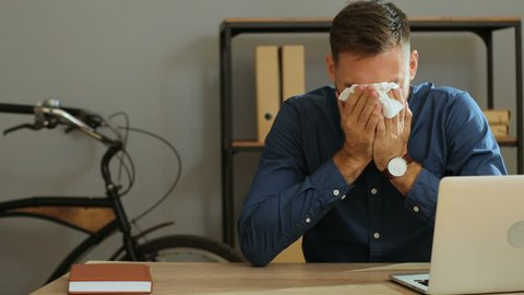 Portrait shot of sad desperate man crying during his work and usining napkins to removing tears in the office.