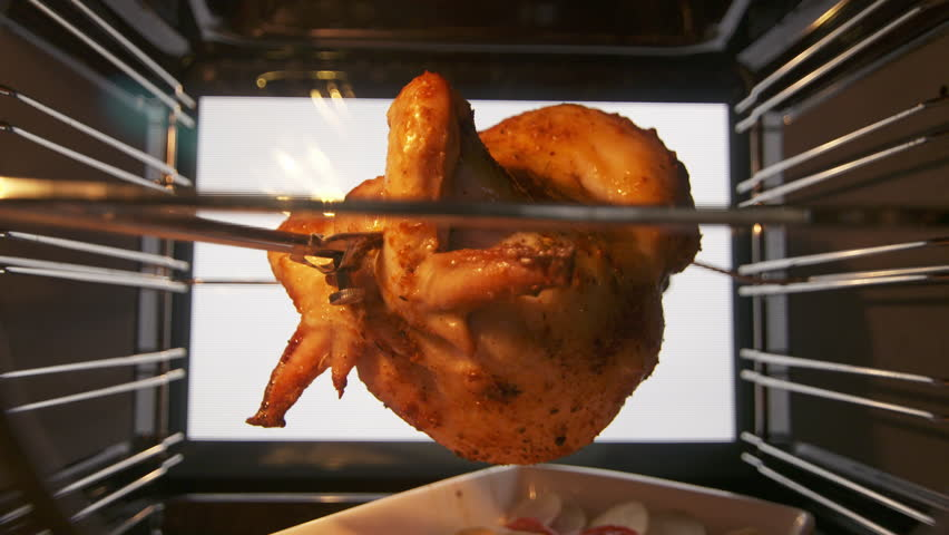 Cooking roasted whole chicken on the rotisserie spit in hot convection oven. Browned chicken rotates during broiling under a grill element. Meat juices dripping onto a baking tray. Inside view.