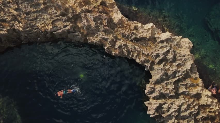 Aerial shot of swimmers in Blue Hole in Gozo, Malta. View from above of snorkelers in blue sea cave and clear water. 4k drone footage of Mediterranean swimming hole with rocks at Azure Window in Malta