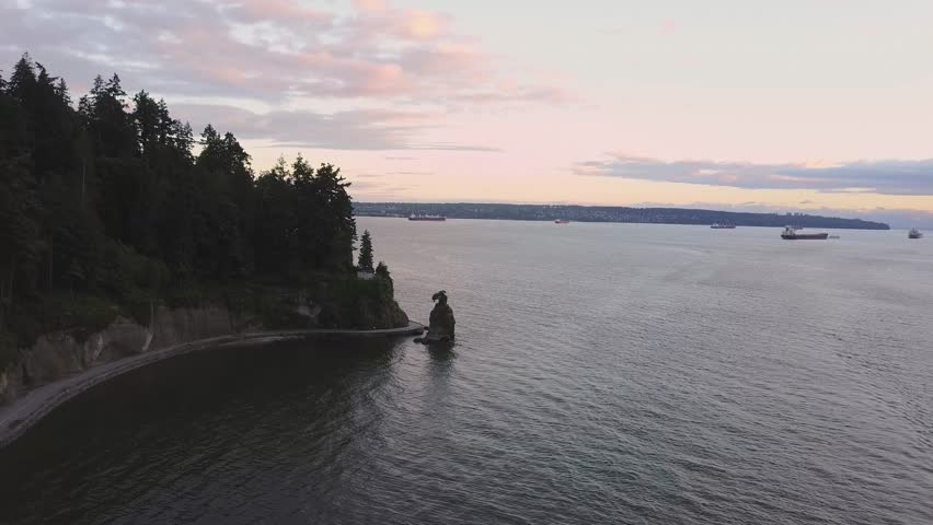 Aerial view of the famous Siwash Rock in Stanley Park, Vancouver, British Columbia, Canada. Taken during a colorful and vibrant cloudy sunset.